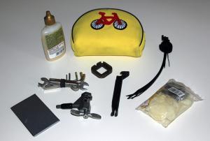 Officina da viaggio: nastro adesivo, attrezzi, olio, fascette, kit di riparazione gomme, il tutto in una pratica borsetta